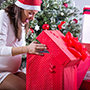 image of woman opening Christmas presents