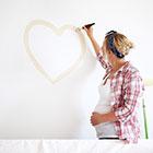 pregnant woman decorating nursery