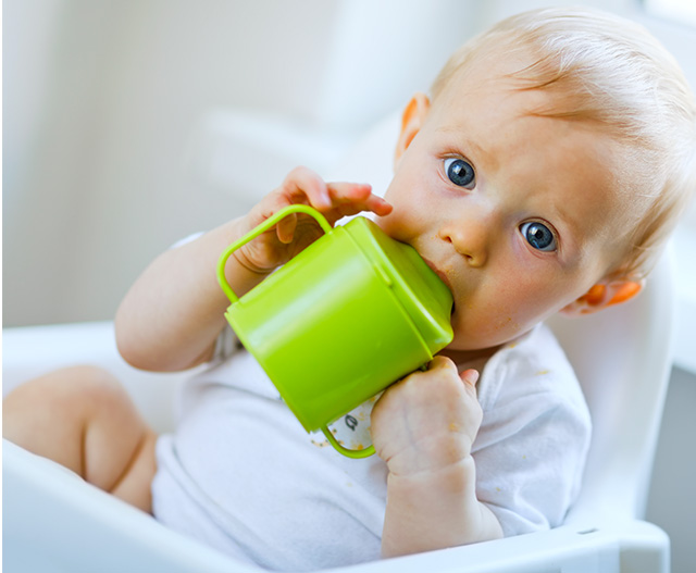 BABY drinking from beaker