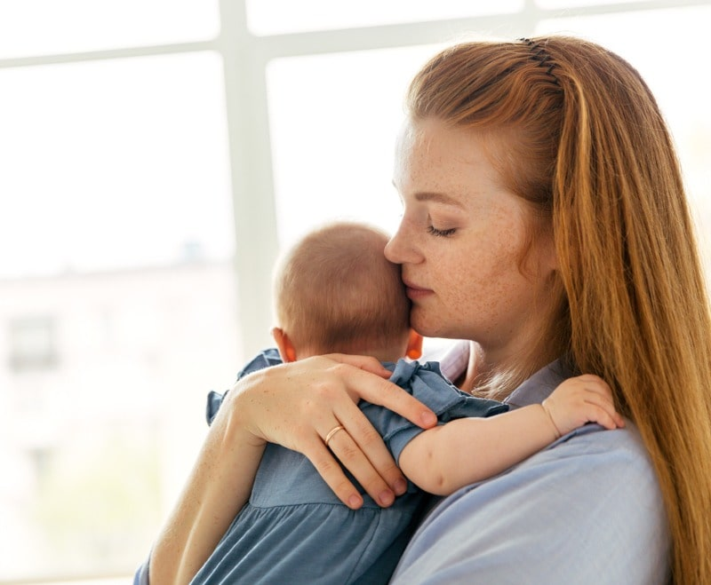 young-mother-with-a-threemonthold-baby-by-the-window-in-the-bedroom-picture-id1217592991-min