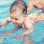 baby being held swimming under water