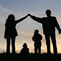 family stood together in sunset