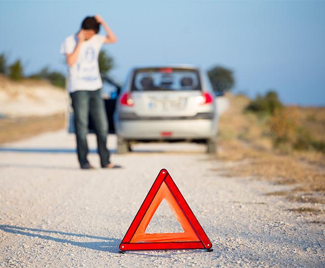 man standing by car, breakdown triangle