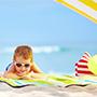 boy laying on beach in sunglasses