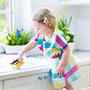 child standing at sink holding sponge