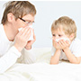 man and child blowing their nose